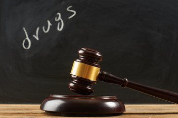 "Judge gavel on wooden table at blackboard background writing the word ""drugs""."