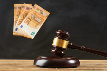 Judge gavel on wooden table at blackboard background with money.