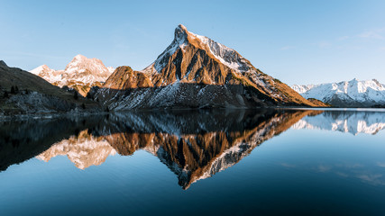 Sunset at a calm mountain lake in Austria with mirror-like reflection