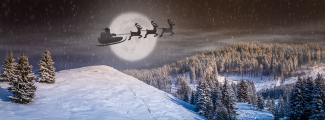 Christmas background, fantastic holiday scene. winter fairytale landscape, wonderland scenery with tree, snow falling, Santa Claus in a sleigh with reindeer flying in the Christmas eve with full moon