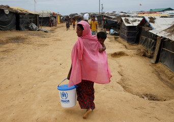 A Rohingya refugee woman heads back towards her temporary shelter after receiving humanitarian aid at Kutupalong refugee camp near Cox's Bazar