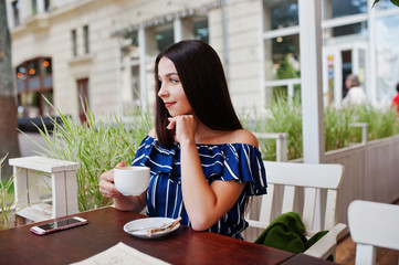 Gorgeous brunette girl sitting on the table in cafe with cup of coffee.