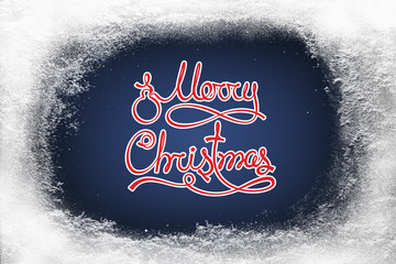 Merry Christmas text on blue background and hoarfrost snow frost on xmas window