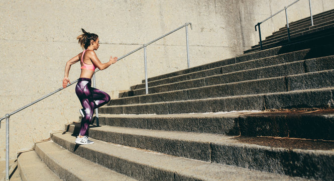 Fitness woman running up on steps