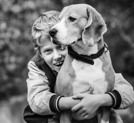 Happy smiling boy hugs his best freind beagle dog