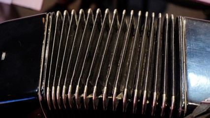 Playing on a big accordion. Playing the harmonica close-up. Old musical instrument Russian bayan - button accordion close-up