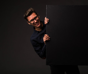 Young cheerful man portrait of a confident businessman showing presentation, pointing paper placard black background. Ideal for banners, registration forms, presentation, landings, presenting concept.