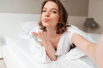 Lady lies on bed indoors home blowing kisses to you.
