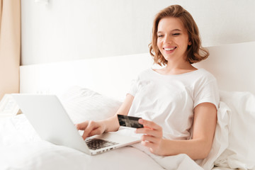 Happy young amazing woman sitting indoors using laptop