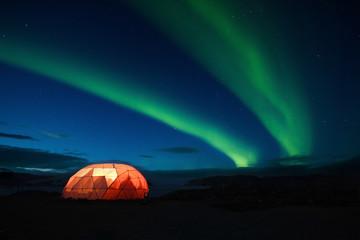 Aurora boreale con tenda illuminata