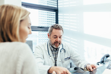 Mature doctor talking with female patient in clinic
