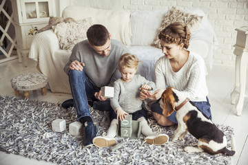 happy family playing with a pet dog in the spacious living room