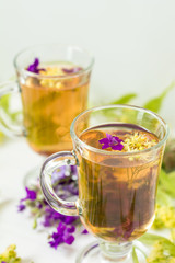 Linden herbal tea in transparent grog glass