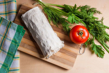 Pita bread or lavash wrapped with cottage cheese or curd, chicken, tomatoes and herbs - dill, onion, parsley on cutting board..