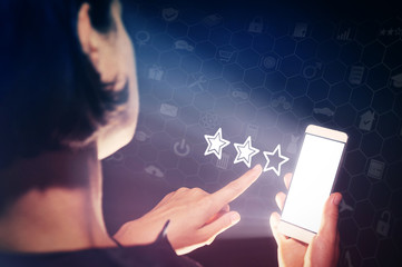 Image of a girl with a smartphone in hands. She presses on the three stars (rating icon). User feedback, quality assessment, product and service ratings.