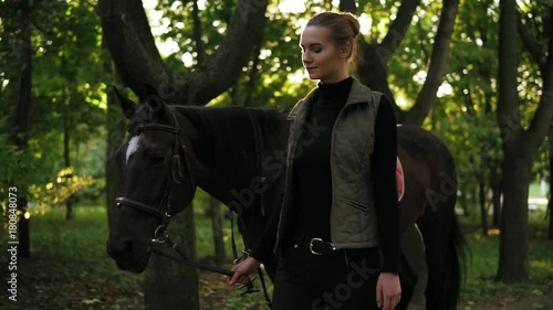 Slowmotion shot of attractive young female jokey walking with brown horse with white spot on forehead in the forest during sunny day in autumn holding leather strap of saddle