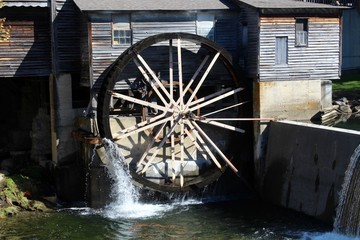 The old water wheel on the side of the wood building.