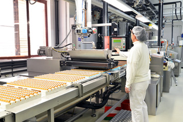 Frau bedient Maschine zum befüllen von Pralinen mit Schokolade in der Lebensmittelindustrie // woman operates machine for filling chocolate pralines in the food industry