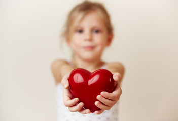 Pretty girl holding big red heart. Concept of love, charity and peace.