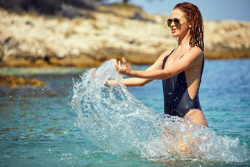 adult slim attractive woman posing in blue waters of Adriatic sea beach on Makarska riviera