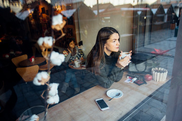 Beautiful brunette young woman in a cafe holding a cup of coffee or cocoa, seen through the window with buildings and lights reflections. She is looking away. Lifestyle concept.