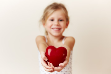 Beautiful smiling girl giving red heart as symbol of love and happiness.