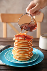 Woman pouring honey onto pancakes with bacon on table