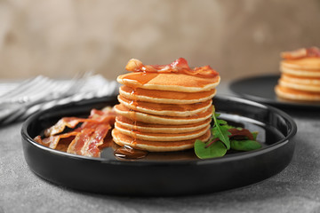 Tasty pancakes with bacon on plate