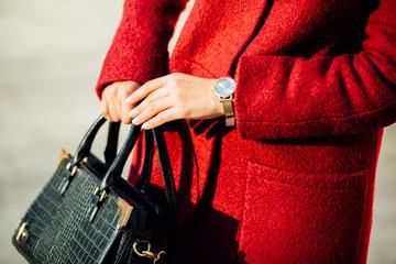 Fashionable woman hold green handbag, watch. Street style city background.