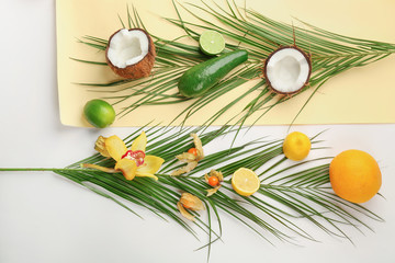Composition with tropical leaves and exotic fruits on white background