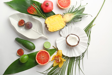 Composition with tropical leaves and exotic fruits on light background