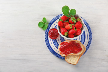 Bread with strawberry jam and bowl of fresh berries on plate