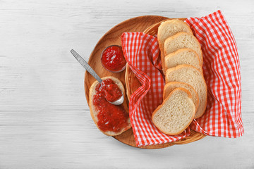 Bread with strawberry jam on wooden plate