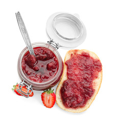 Jar and bread with strawberry jam on white background