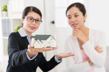 advisor woman and investor looking at house model