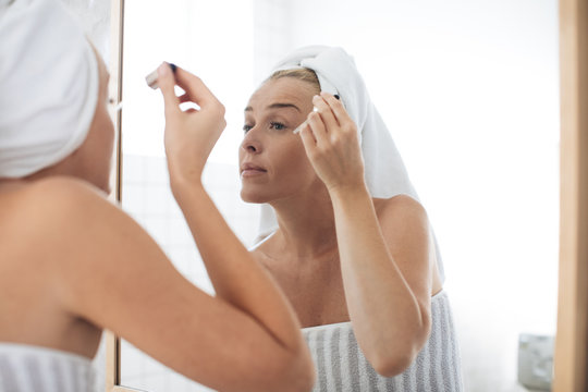 Woman Putting Cosmetic Serum on Her face