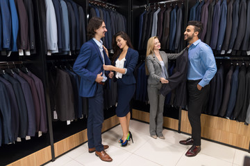 Successful Business Men Choosing New Suits With Attractive Female Sellers Offering Elegant Clothes, Male Buyers In Modern Store