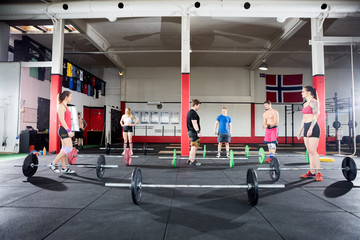 Men And Women With Barbells In Fitness Center