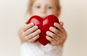 Close-up of little girl holding heart in her hands. Concept of help, care and support.