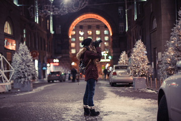 Hipster girl walking through the night city street taking photos of buildings and Christmas trees