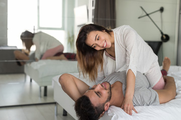 Couple Embracing Lying In Bed, Young Woman Sit On Man In Bedroom Love And Relationship Concept