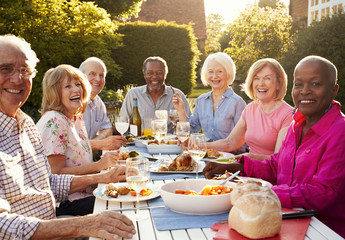 Portrait Of Senior Friends Enjoying Outdoor Dinner Party At Home
