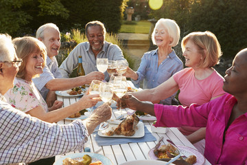 Group Of Senior Friends Making A Toast At Outdoor Dinner Party