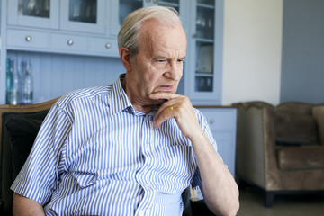 Senior Man Sitting In Chair At Home Suffering From Depression
