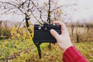 photographer holding 35mm retro film camera. vintage effect