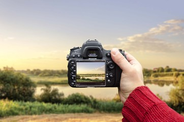 hand holding dslr camera capturing lake landscape