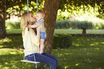 Mother Kissing Baby Son As They Sit On Garden Swing