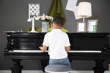 Little African-American boy playing piano indoors