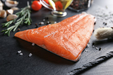 Slate plate with salmon fillet on table