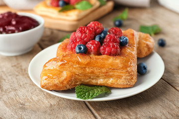 Plate with delicious pastry on wooden table